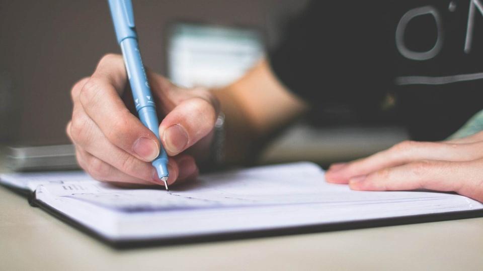 Concurso Luiziana - PR: foco em pessoa escrevendo em caderno