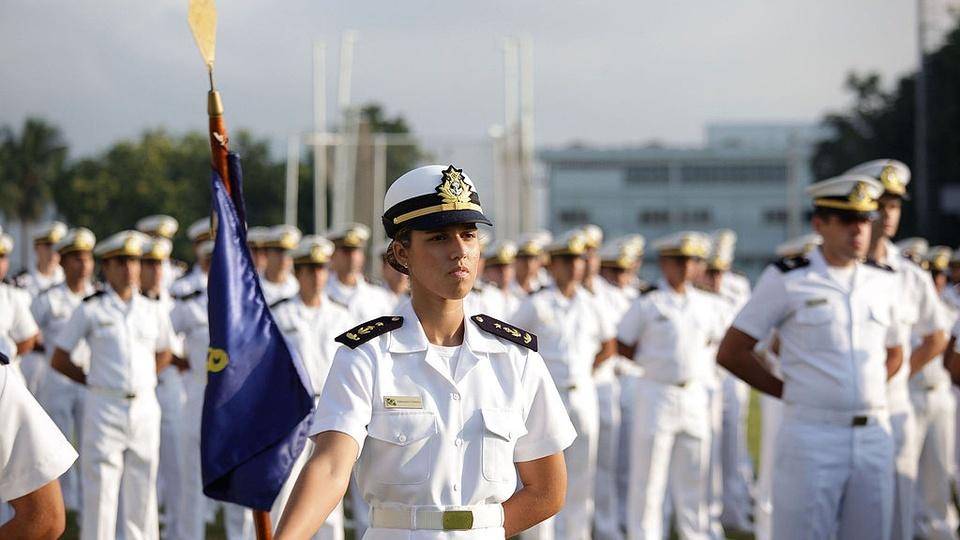 Concurso Marinha: militares navais em formação ao fundo e militar naval à frente segurando bandeira