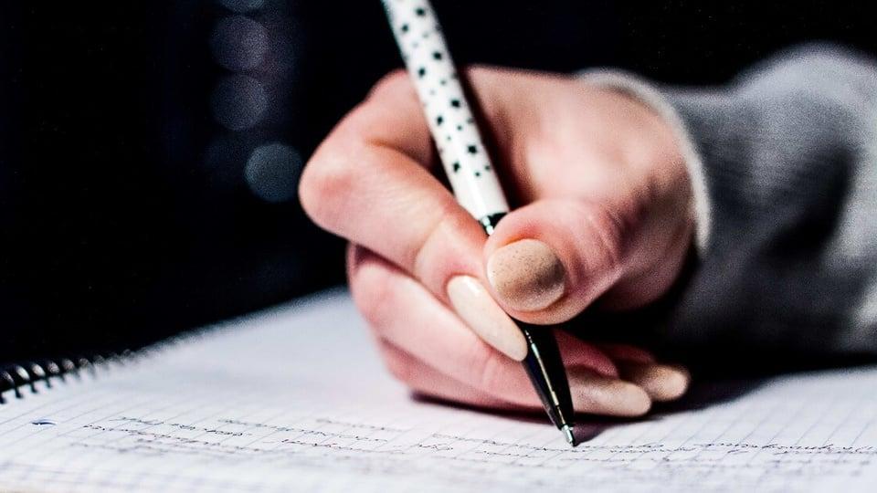Concurso MP ES: enquadramento em mão escrevendo em caderno