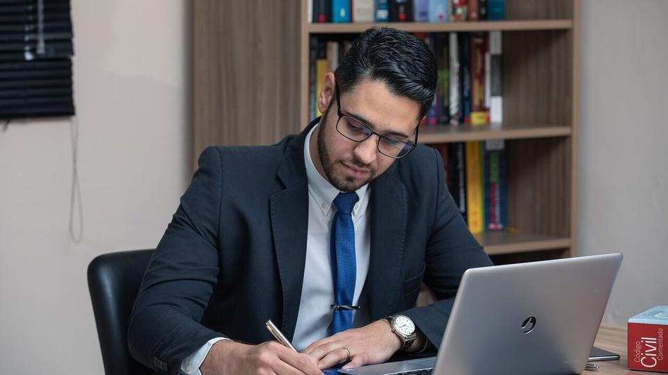Concurso MP GO: a foto mostra um profissional do Direito trabalhando em seu escritório