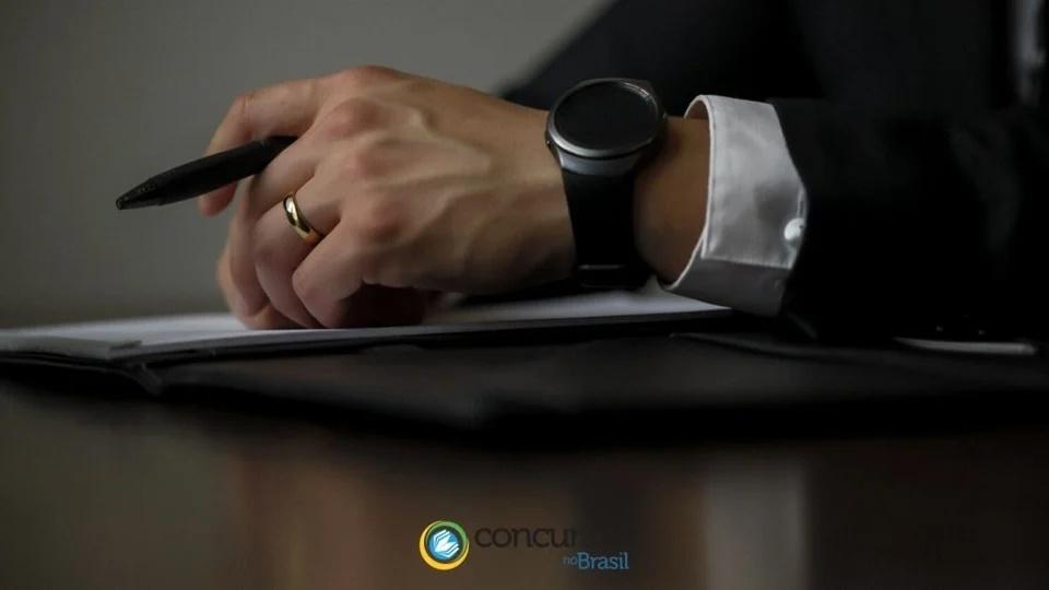 Concurso MP RS: a foto mostra mão masculina com relógio de pulso, aliança e caneta
