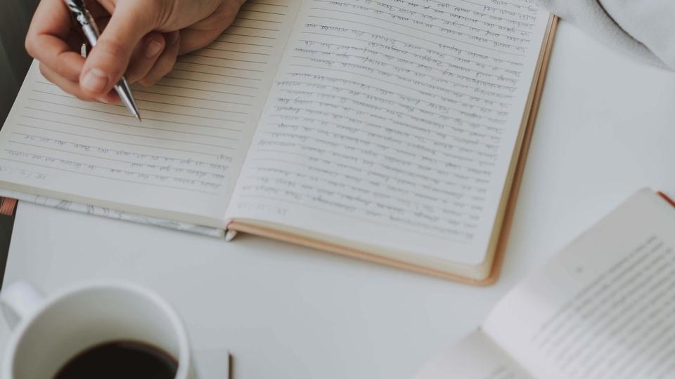 Concurso Novo Mundo - GO: caderno, livro e xícara de café sob superfície; pessoa escreve em caderno