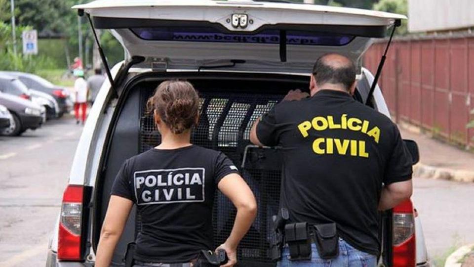 concurso PC DF: a imagem mostra dois policiais civis olhando o porta-malas de uma viatura