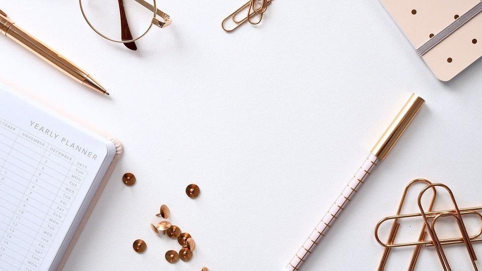 Concurso PC TO: a foto mostra objetos dourados de escritório: caneta, lápis, clips, papel, óculos