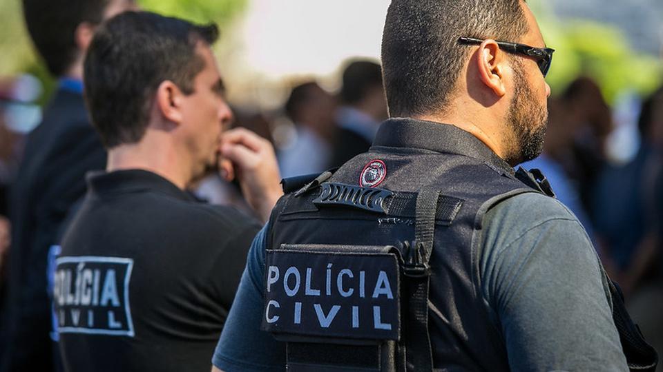 Justiça decide manter suspensão das provas do concurso PCDF: é possível ver dois policiais civis. Eles estão de costas para a câmera