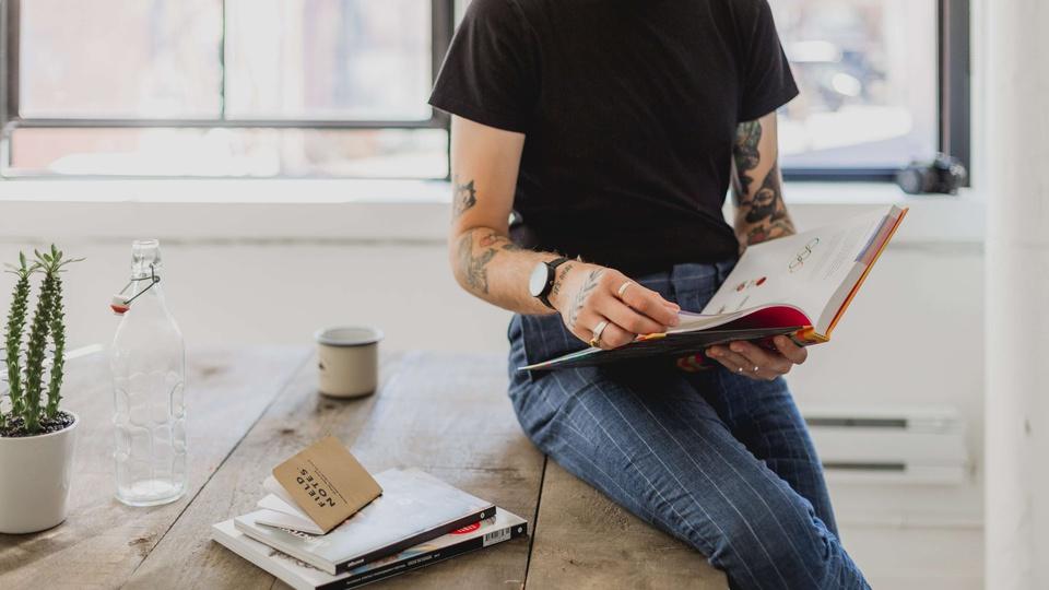 Concurso Pedregulho - SP: homem sentado em mesa lendo livro