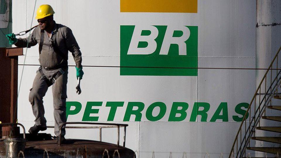 Petrobras: ao fundo logomarca da empresa pública; na frente um homem trabalhando
