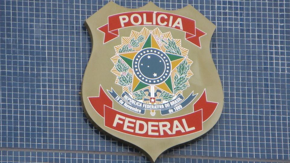 Suposto cronograma traz as datas do concurso PF: logo da Polícia Federal. Ela está disposta em parede com cerâmica azulada