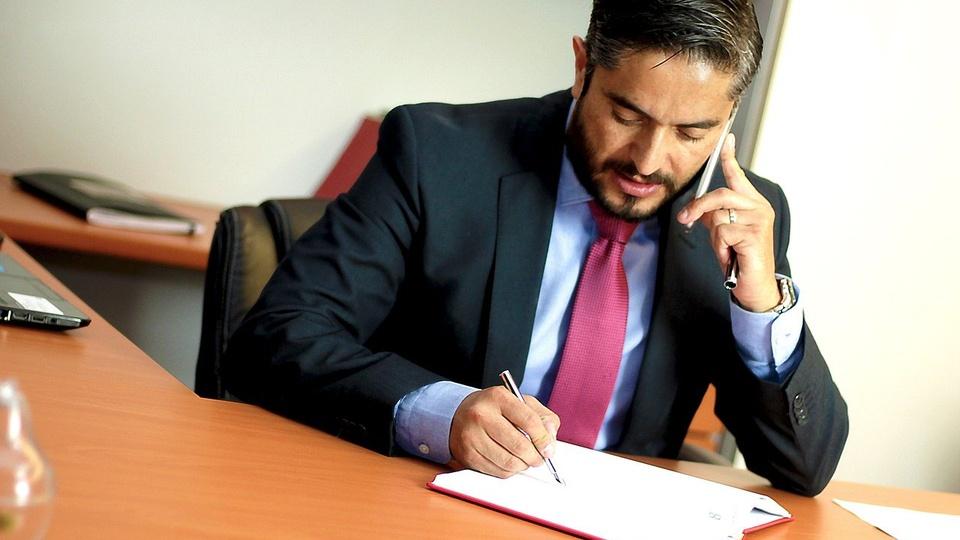 Processo seletivo PGE - MS: homem de terno e gravata fala ao celular enquanto escreve em folha de papel.