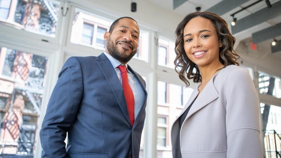 concurso pge rj: a imagem mostra homem e mulher vestidos de terno e sorrindo