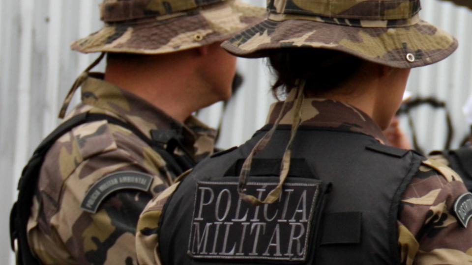 """Edital do concurso PM PI poderá ficar para depois de outubro de 2020: dois policiais militares de costas para a câmera. Na parte detrás de um dos uniformes, é possível ler """"Polícia Militar"""""""