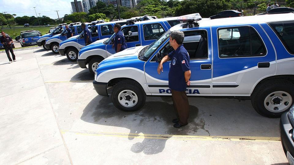 Concurso Polícia Civil - BA: a foto mostra viaturas da polícia civil da Bahia, cada uma com um policial ao lado