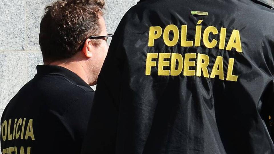 concurso policia federal: a imagem mostra dois agentes da pf virados de costas