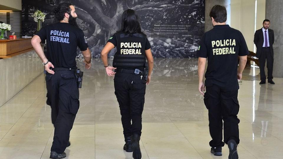 concurso polícia federal: a imagem mostra três policiais federais de costas andando