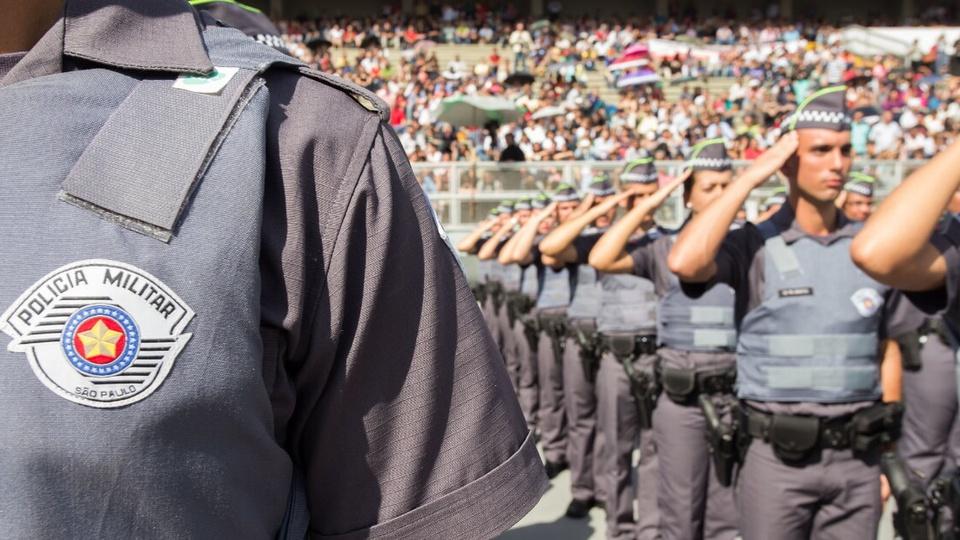 Piso salarial Polícia Militar será analisado pelo Congresso: destaque para pessoa usando uniforme da Polícia Militar de São Paulo. É possível ver somente parte da vestimenta no primeiro plano da câmera. Atrás, policiais estão em posição de continência