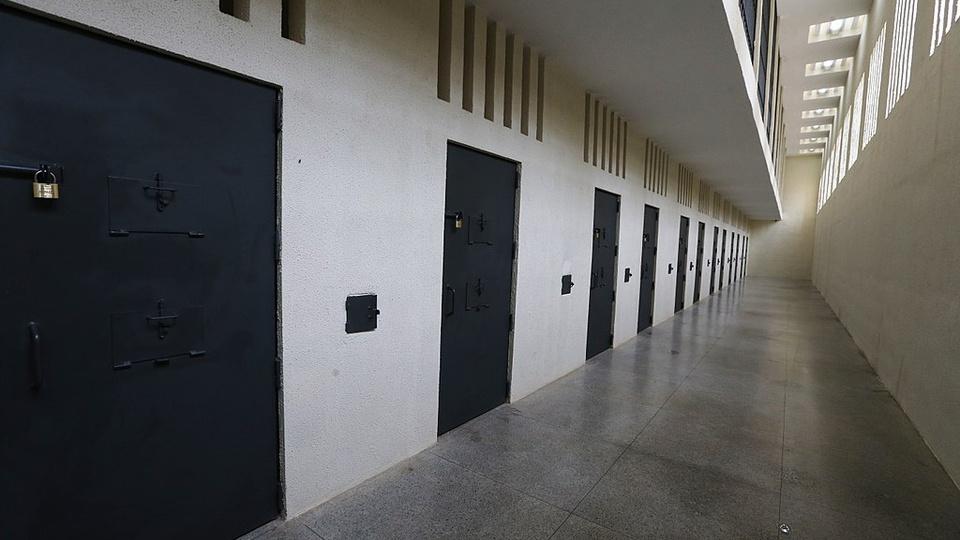 Concurso Polícia Penal PE: corredor com várias portas de metal trancadas com cadeados