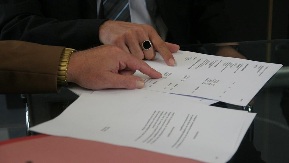 Concurso PPGG DF: a foto mostra um enquadramento em que pessoas estão lendo um contrato, não são mostrados rostos, apenas as mãos de duas pessoas com um dos dedos apontando o documento