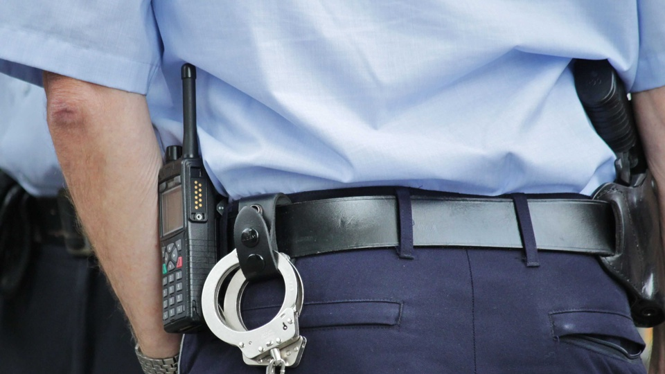 Concurso Prefeitura Catas Altas: guarda municipal virado de costas, com algemas e rádio comunicador presos ao cinto
