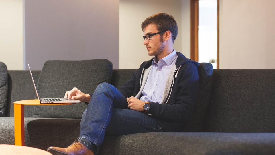 Concurso Prefeitura da Lapa - PR: homem está sentado em sofá usando notebook