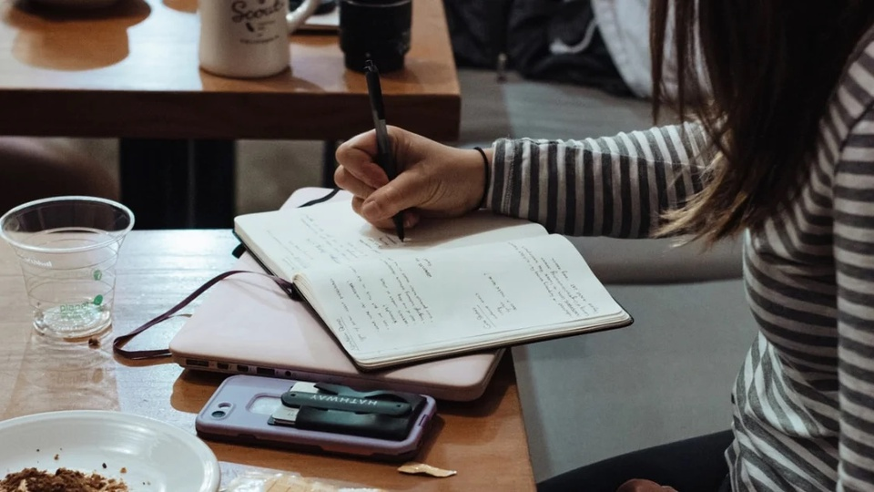 Concurso Prefeitura de Águas Frias - SC: a foto mostra pessoa fazendo anotações em um caderno em cima de uma mesa, onde há celular, prato e outros objetos