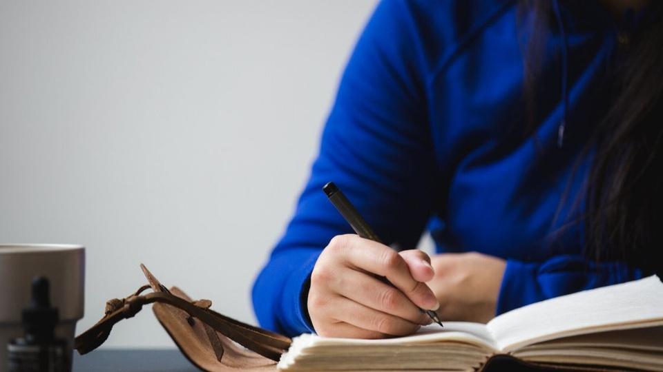 Concurso Prefeitura de Águas Mornas: pessoa com uma blusa azul escrevendo em um caderno
