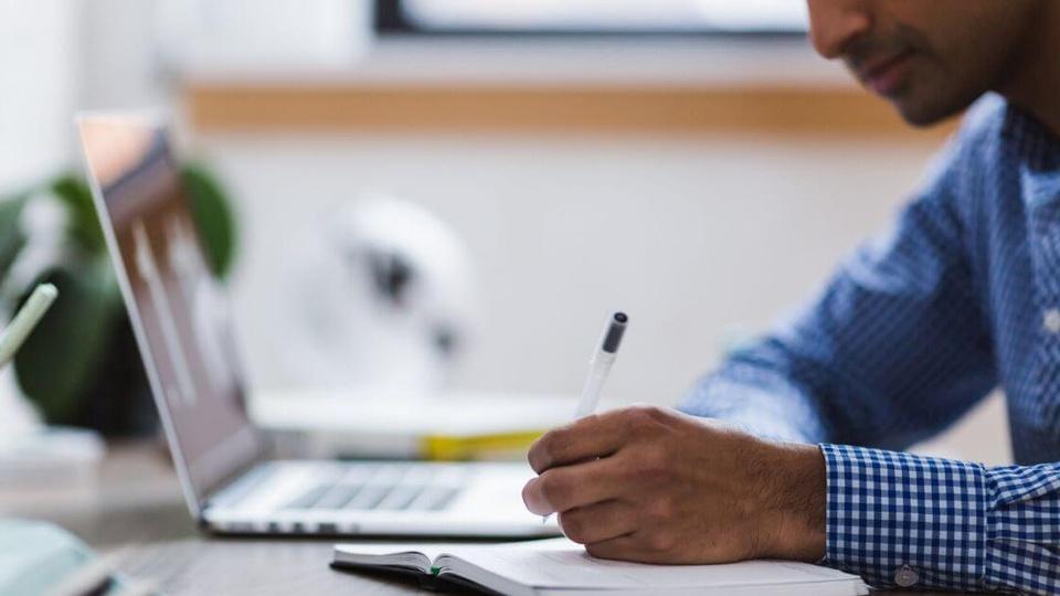 Concurso Prefeitura de Almirante Tamandaré do Sul - RS:  mão de homem negro escrevendo com caneta transparente em um caderno, o notebook ao lado dele
