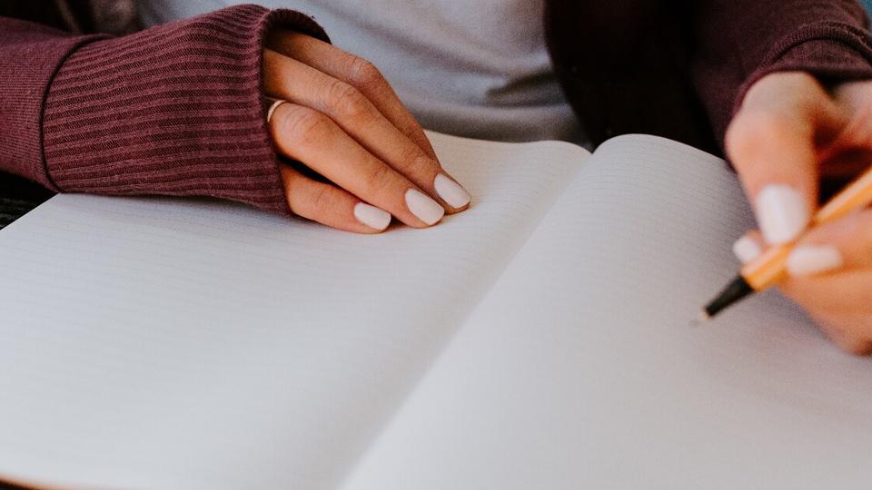 Concurso Prefeitura de Antônio Carlos: mulher escrevendo em um caderno que está disposto sobre uma mesa. A imagem corta o rosto da mulher e só é possível ver do antebraço para baixo