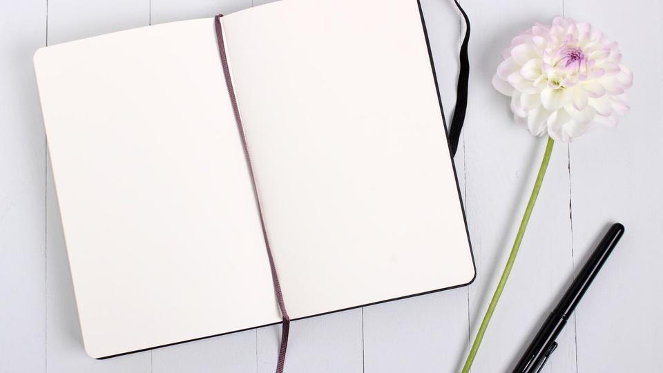 Processo seletivo Prefeitura de Bandeirante - SC: caderno aberto com caneta e flor ao lado