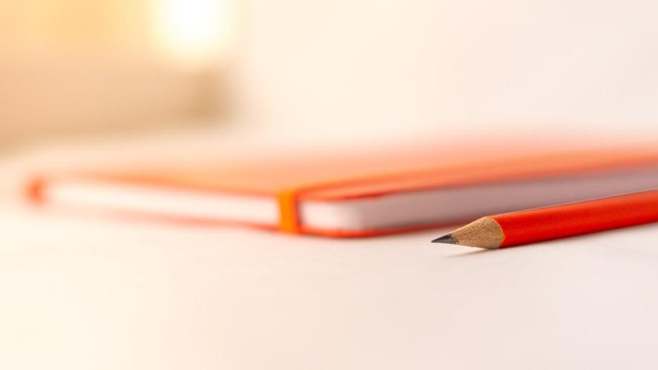 Concurso Prefeitura de Barueri: a imagem mostra caderninho de capa laranja fechada com lápis ao lado