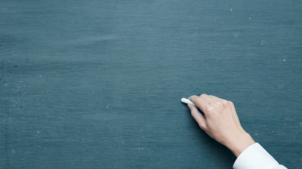 Concurso Prefeitura de Belo Horizonte: foto de uma mão com um giz escrevendo em uma lousa