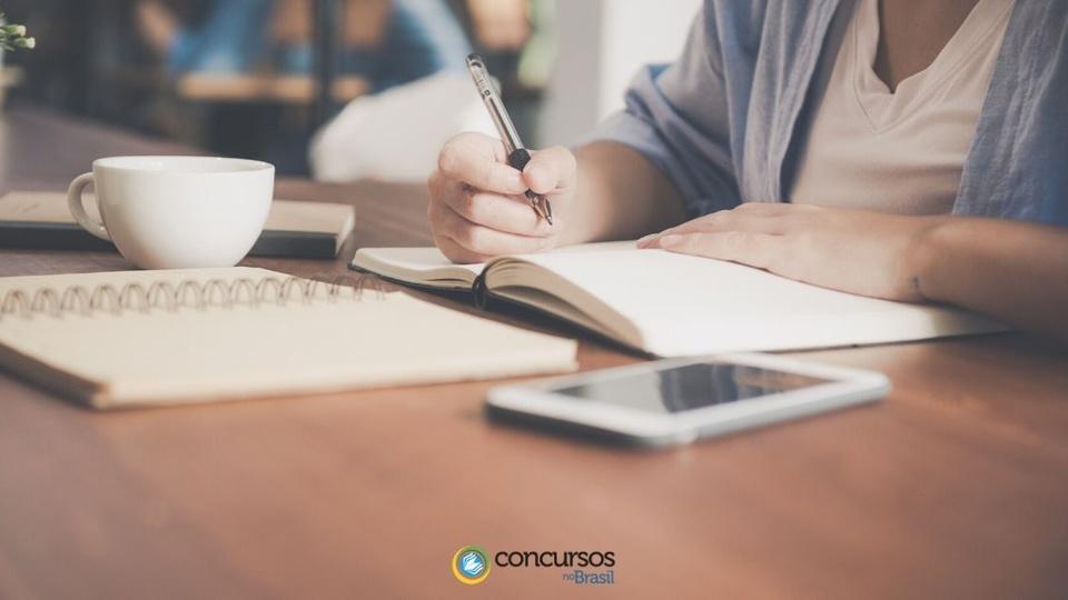Concurso Prefeitura de Bertópolis - MG: pessoa escreve em caderno