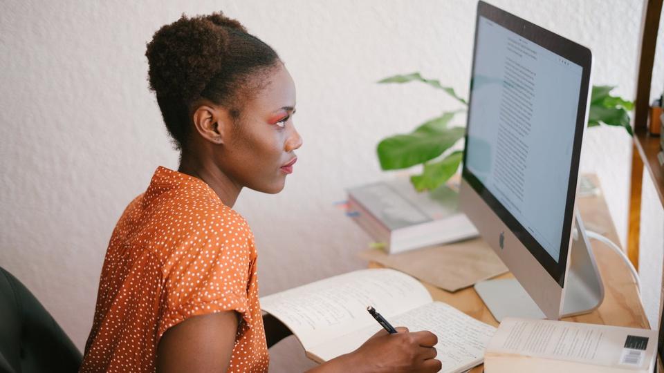 Concurso Prefeitura de Bom Jesus dos Perdões - SP: mulher olhando tela do computador e escrevendo em agenda