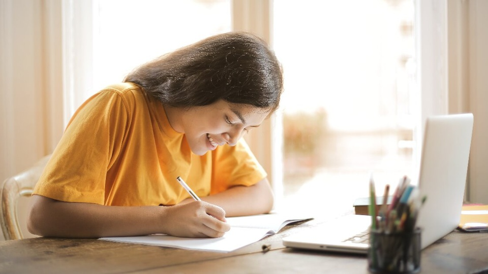 Concurso Prefeitura de Cafelândia - SP: jovem, com os cabelos soltos e jogados para trás, escrevendo em um caderno disposto em mesa. Ela está sentada