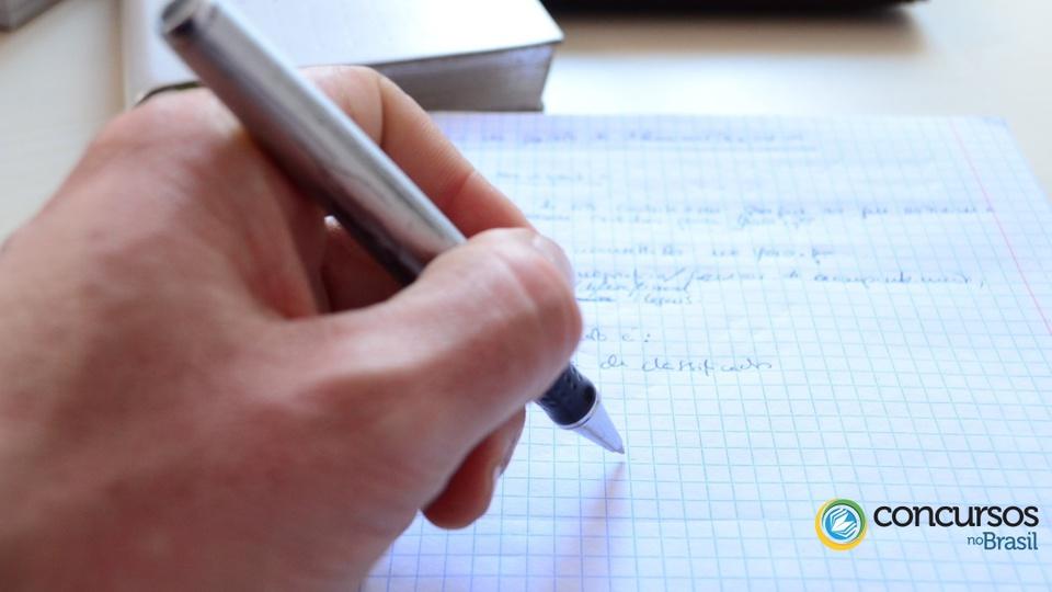 Concurso Prefeitura de Campos Novos: a foto mostra caneta na mão de uma pessoa escrevendo sobre um papel