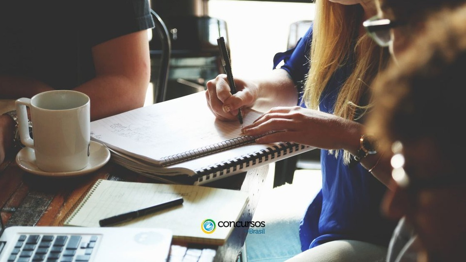 Concurso Prefeitura de Carmo do Cajuru: mulher escrevendo em um caderno sobre a mesa. Ela está rodeada por outras pessoas.
