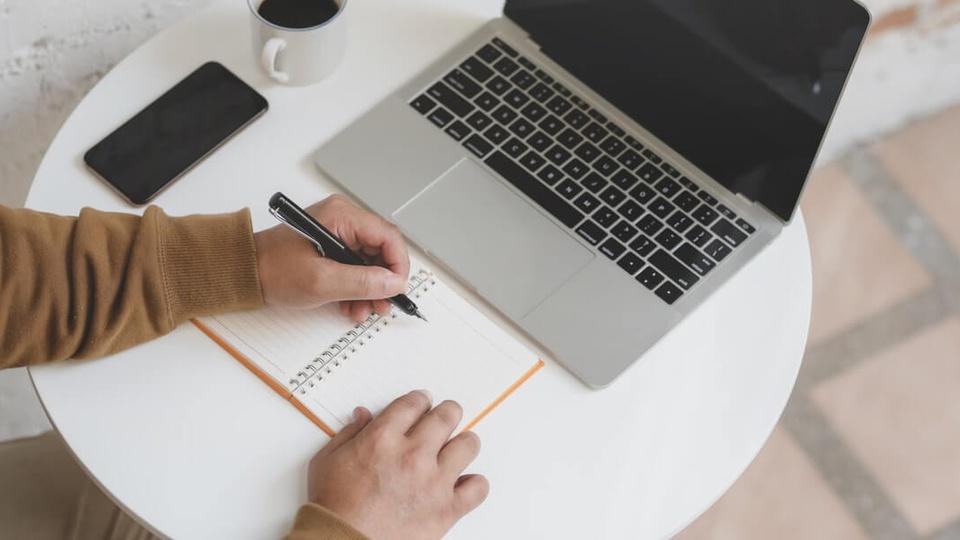 Concurso Prefeitura de Chapadão do Lageado: a imagem mostra pessoa escrevendo algo em caderno em frente a notebook aberto com celular ao lado