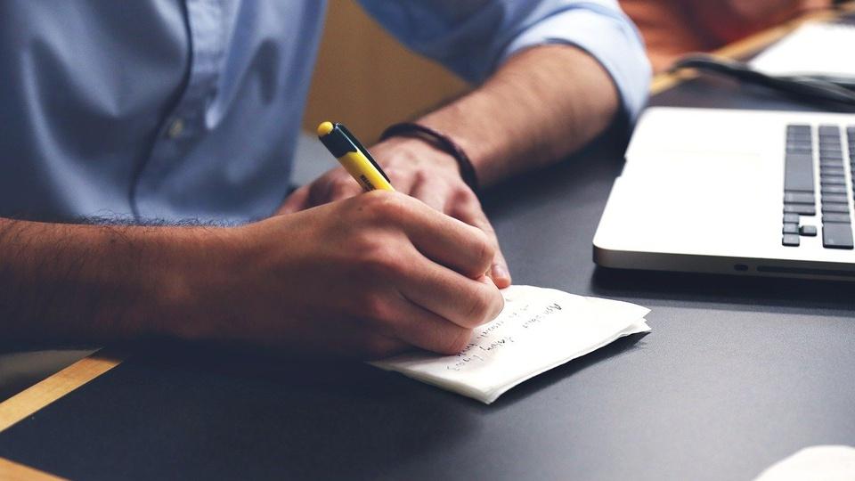 Concurso Prefeitura de Corbélia - PR, pessoa escrevendo em um bloco com um notebook ao lado