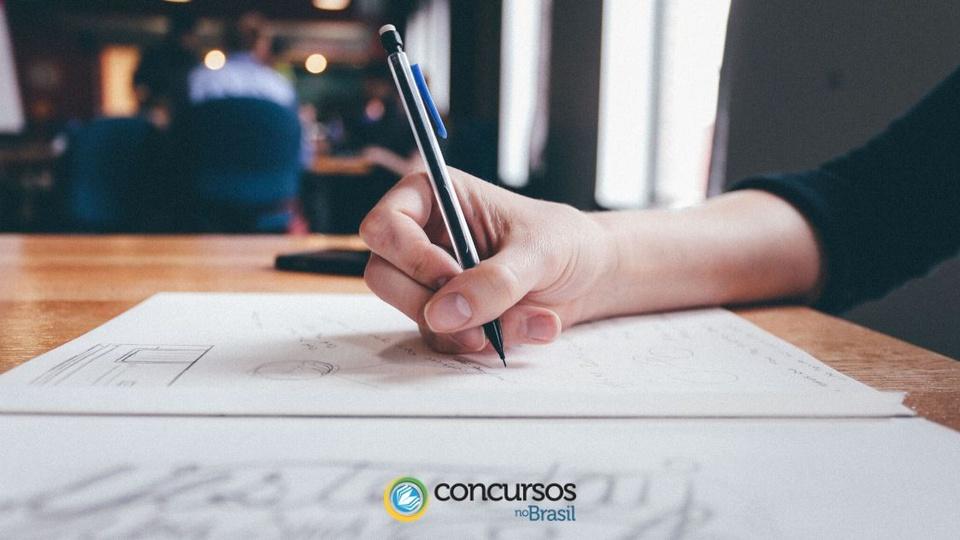 Concurso Prefeitura de Cornélio Procópio: o plano mostra uma mão de pessoa segurando uma caneta e escrevendo em um caderno