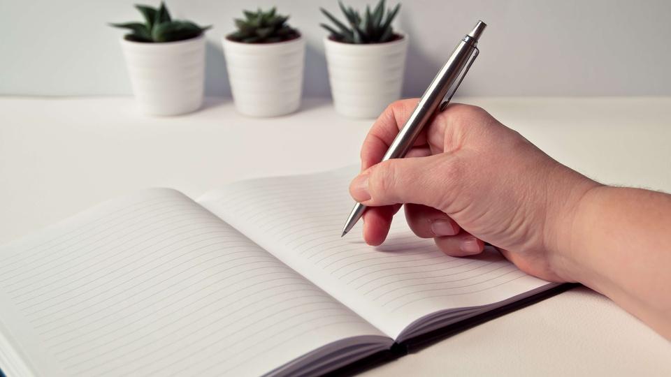 Concurso Prefeitura de Corumbataí - SP: a foto mostra caderno sobre uma mesa, jarros de plantas ao fundo, uma mão segurando uma caneta e pronta para escrever