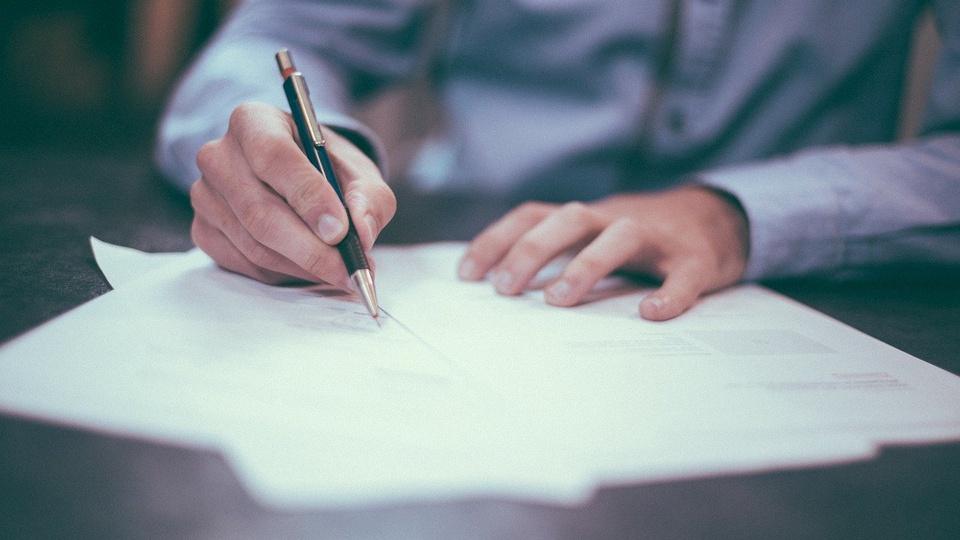 Concurso Prefeitura de Costa Marques - RO: foco em mãos masculinas escrevendo em folha de papel
