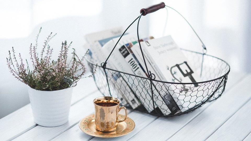 Concurso Prefeitura de Diadema: cesta gradeada com alguns livros empilhados, uma xícara em um pires e um jarro de planta, tudo isso sobre uma mesa branca e em um ambiente bem iluminado, luz do dia