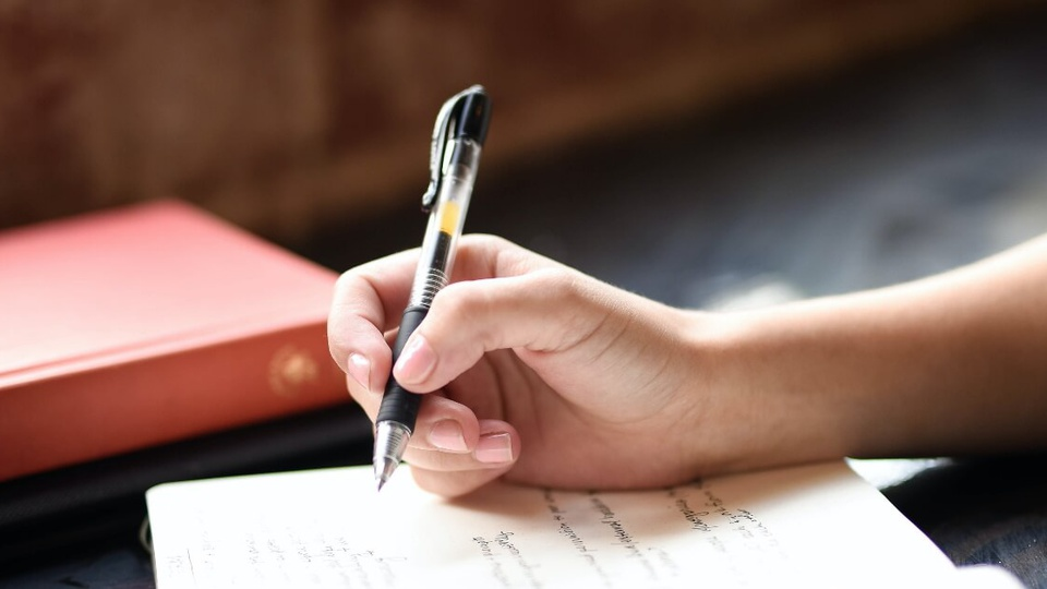 Concurso Prefeitura de Frederico Westphalen - RS: #PraCegoVer mão, com unhas pintadas de rosa claro, segurando uma caneta com detalhes em preto. Está prestes a escrever alguma coisa em uma caderneta