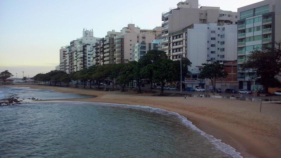 Concurso Prefeitura de Guarapari: a foto mostra uma praia com a água de um lado e uma rua com prédios residenciais de outro
