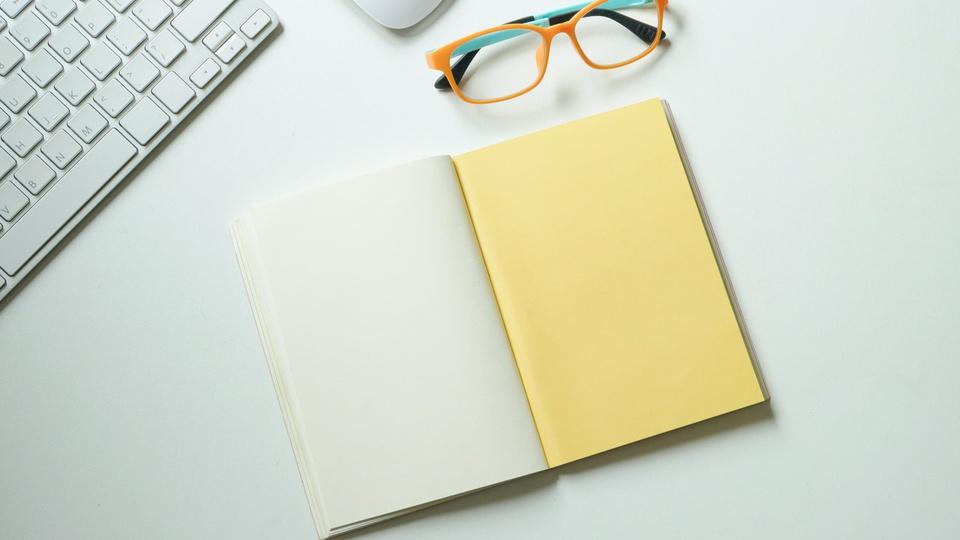 Concurso Prefeitura de Irati:  caderno, óculos, teclado e mouse sobre mesa branca