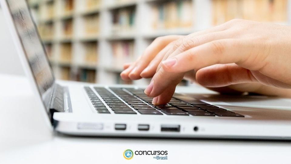 concurso prefeitura de itajaí - sc: foco em mãos digitando em teclado de notebook
