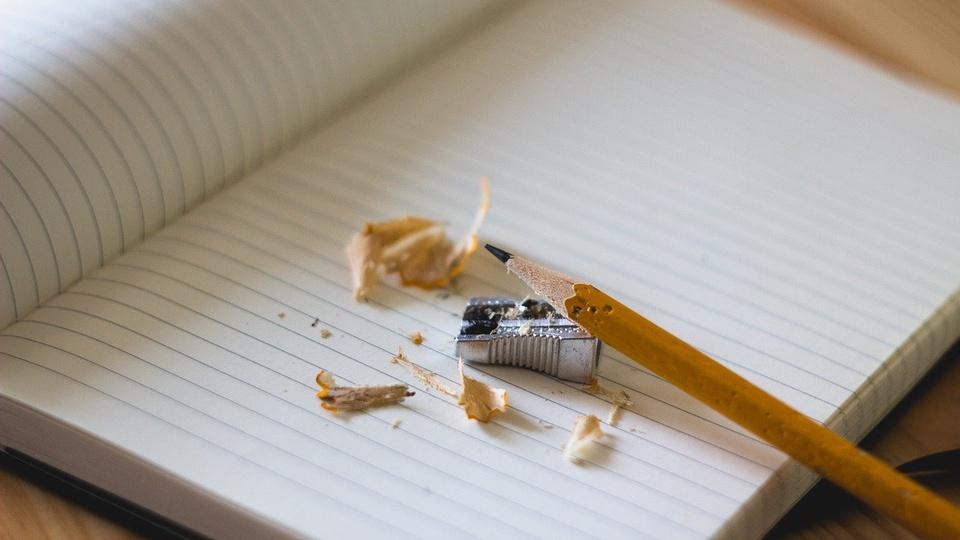 Concurso Prefeitura de Itapiranga - SC: #PraCegoVer a imagem mostra lápis cor marron claro em cima de um caderno, com a ponta afiada, uma lapizeira com prata e restos do apontamento do lápis em cima do caderno