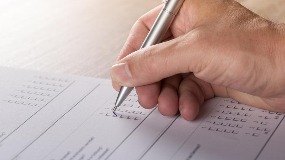 Concurso Prefeitura de Jatobá: mão de uma pessoa segurando caneta e marcando gabarito de prova