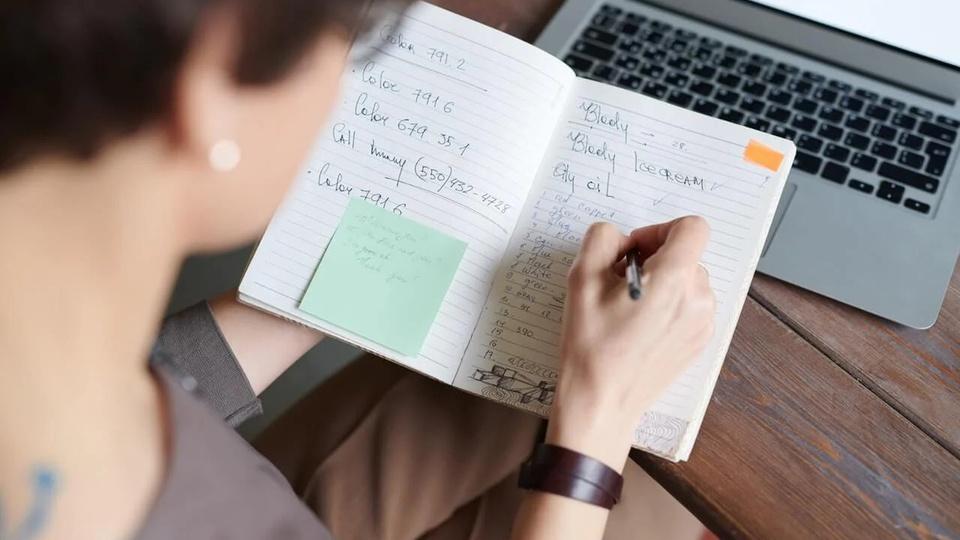 Concurso Prefeitura de Juiz de Fora: a  imagem mostra uma mulher de cabelo curto e brinco na orelha, sentada em frente a computador anotando algo em caderno