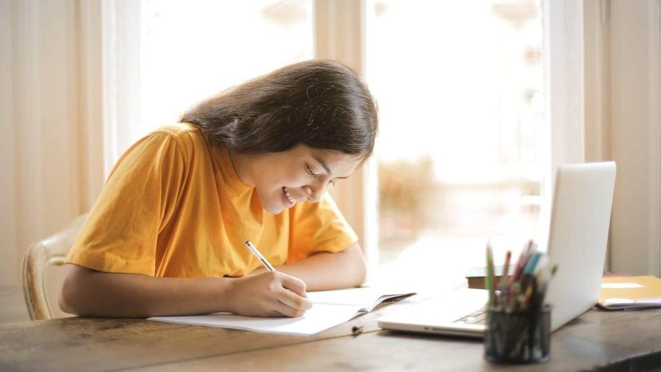 Concurso Prefeitura de Lagoa Dourada - MG: mulher sorridente escrevendo em papel