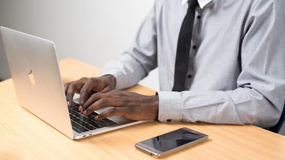 Concurso Prefeitura de Magalhães Barata - PA: homem digitando no notebook e com celular ao lado